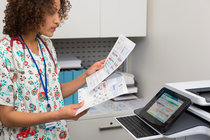 Nurse reviewing her prints from the HP PageWide Enterprise Color MFP 586z.