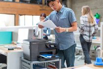 Man checking his prints from a HP Officejet Pro 8710 All-in-One Printer.