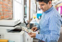 A HP Color LaserJet Enterprise Flow MFP M577z printer at a print station with man printing through N